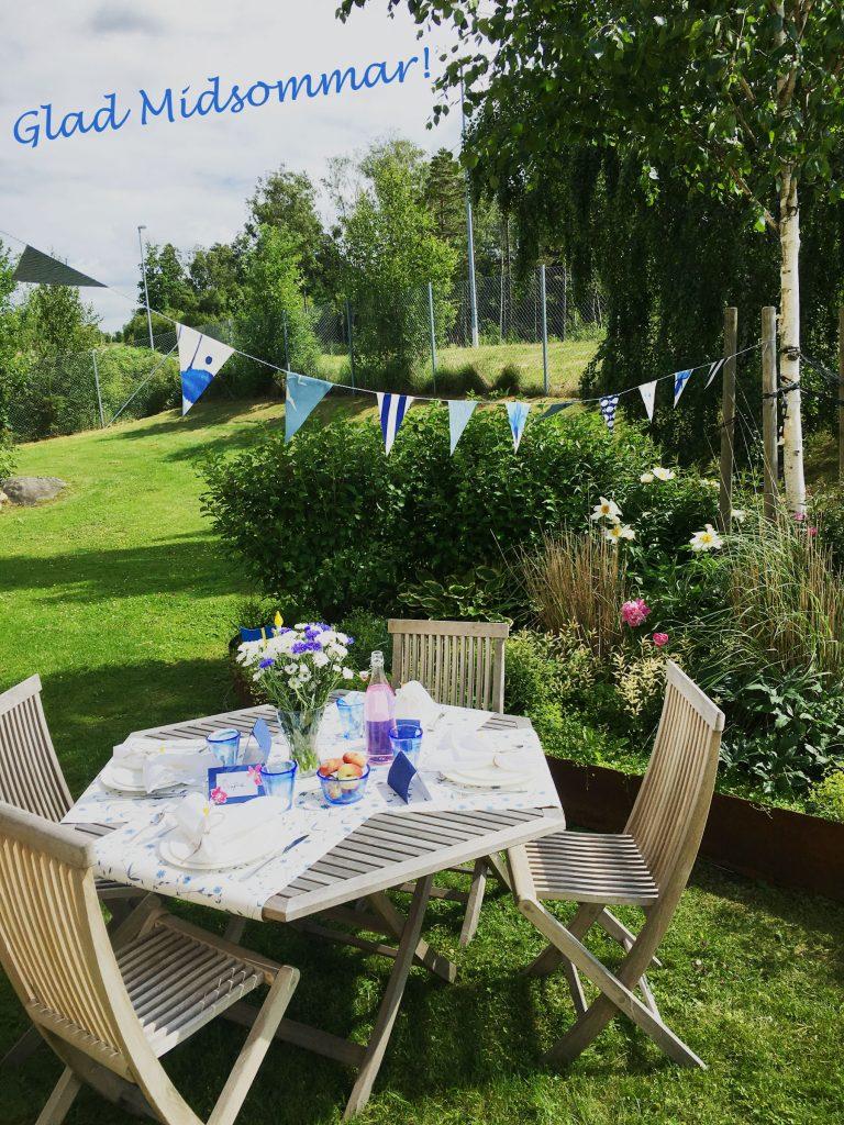 blå-tapeter-glad-midsommar-dukning-bords-blommor-vimpe-midsommarlunch